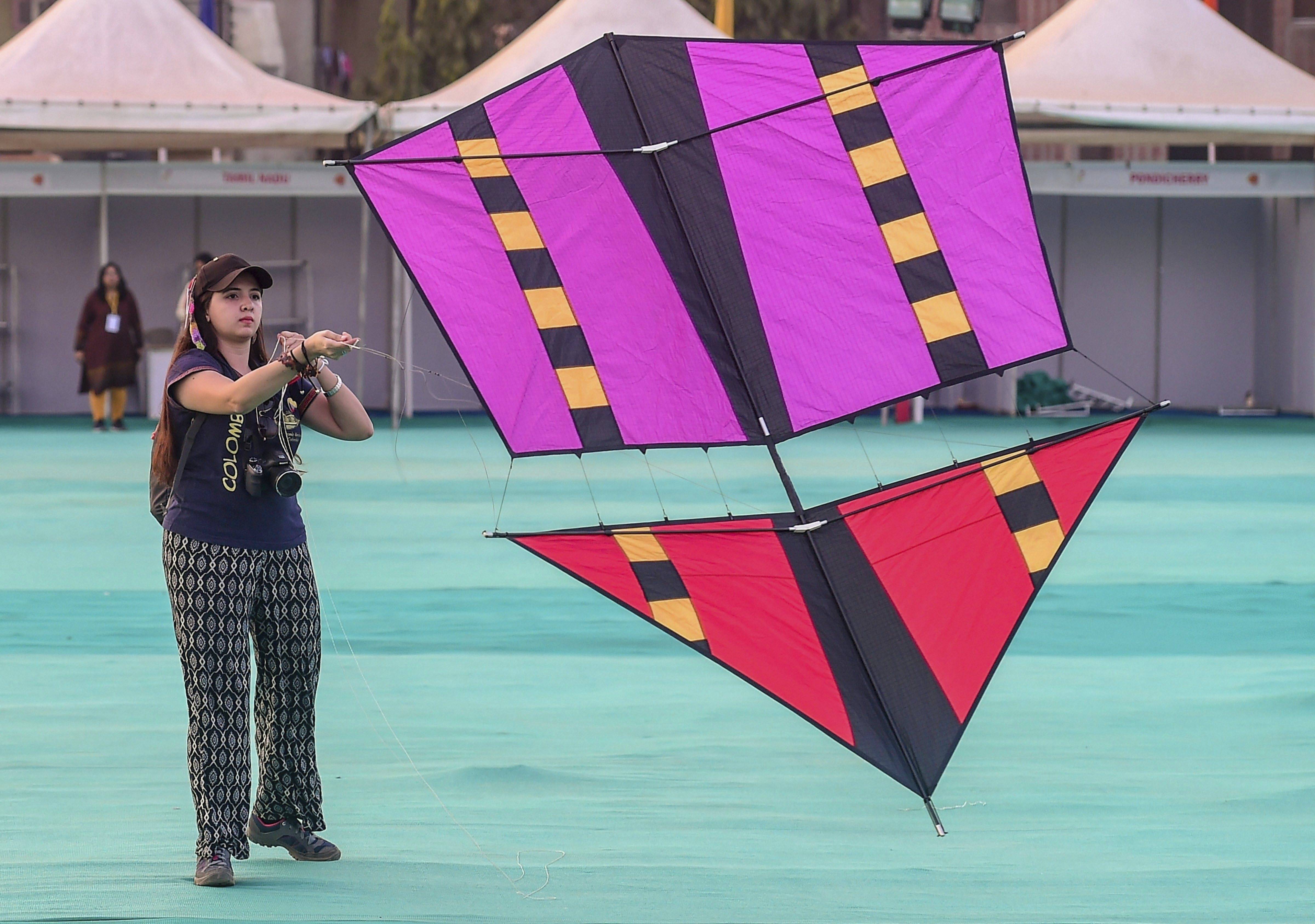 A participant prepares her kite for flying on the eve of the International Kite Festival in Ahmedabad - PTI