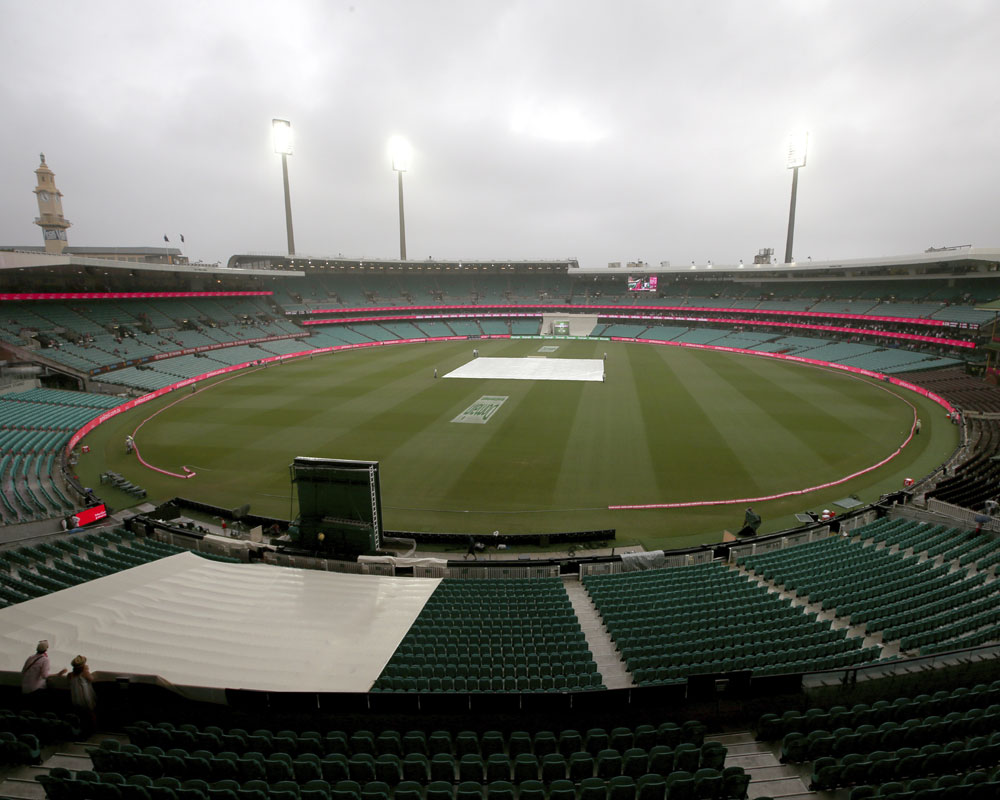 A tarpaulin covers the pitch as rain begins to fall on day 3 of the cricket test match between India and Australia in Sydney - AP
