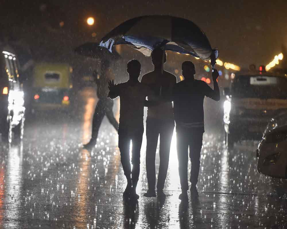 People walk on a road during monsoon rainfall, at Rajpath in New Delhi