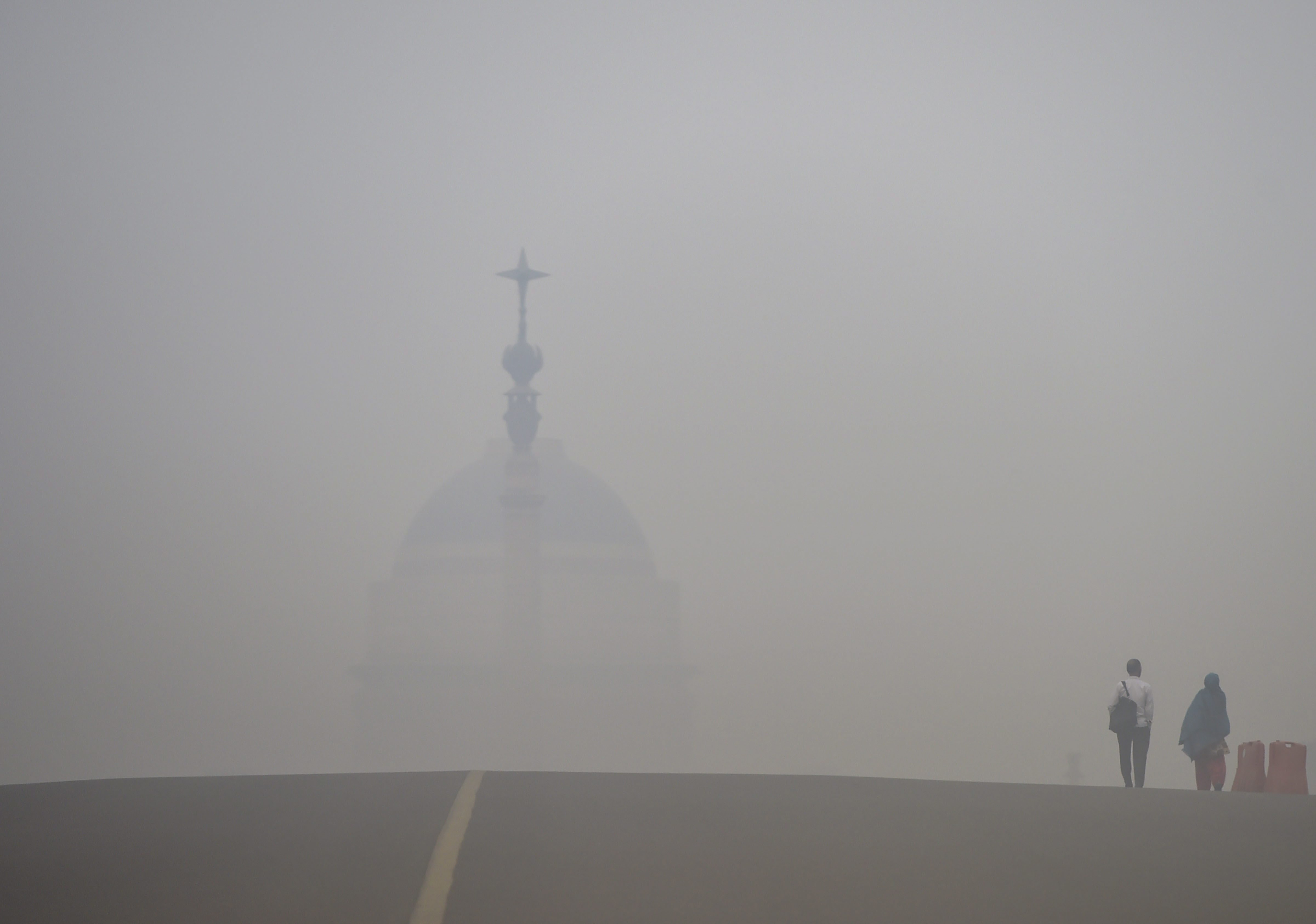 People walk on Rajpath road engulfed in thick haze, in New Delhi - PTI
