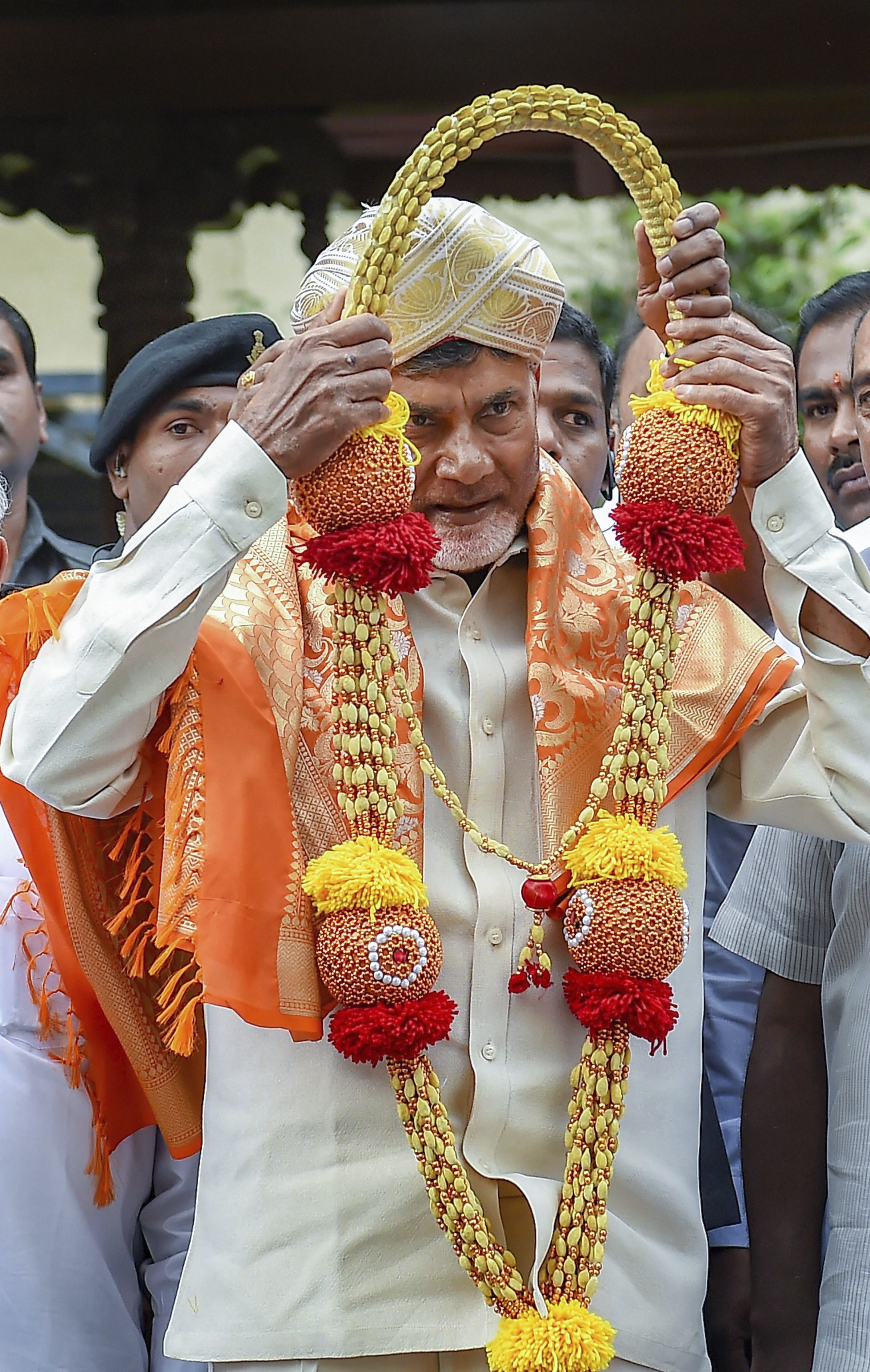 Andhra Pradesh Chief Minister N Chandrababu Naidu wears a Mysore peta and a garland presented to him by JD(S) chief and former prime minister HD Devegowda (unseen) during a meeting in Bengaluru - PTI