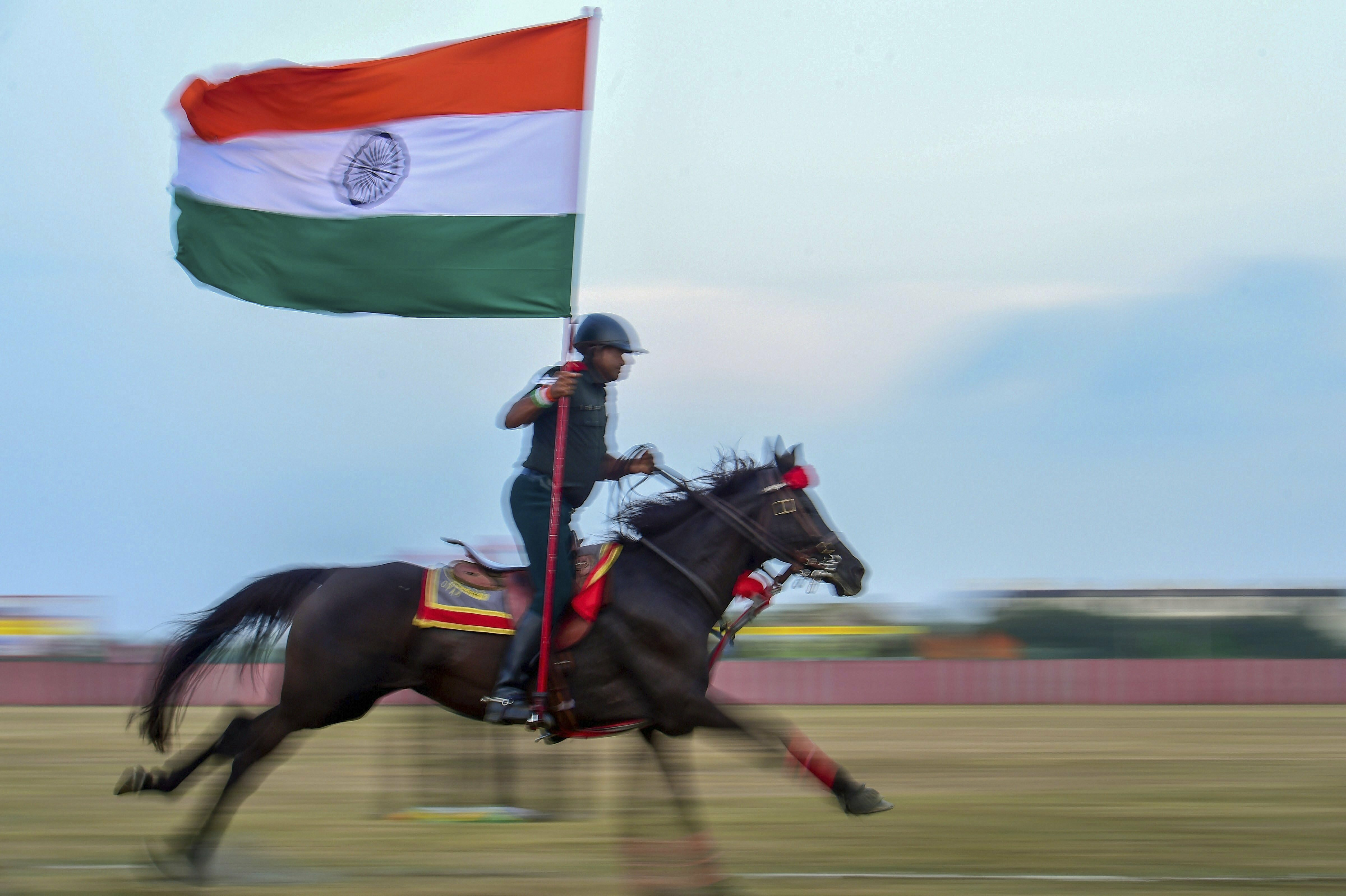 An army personnel holding the Tricolor displays his horse riding skill during the combined display of martial arts and combat skills by the cadets at Officers Training Academy (OTA) in Chennai - PTI