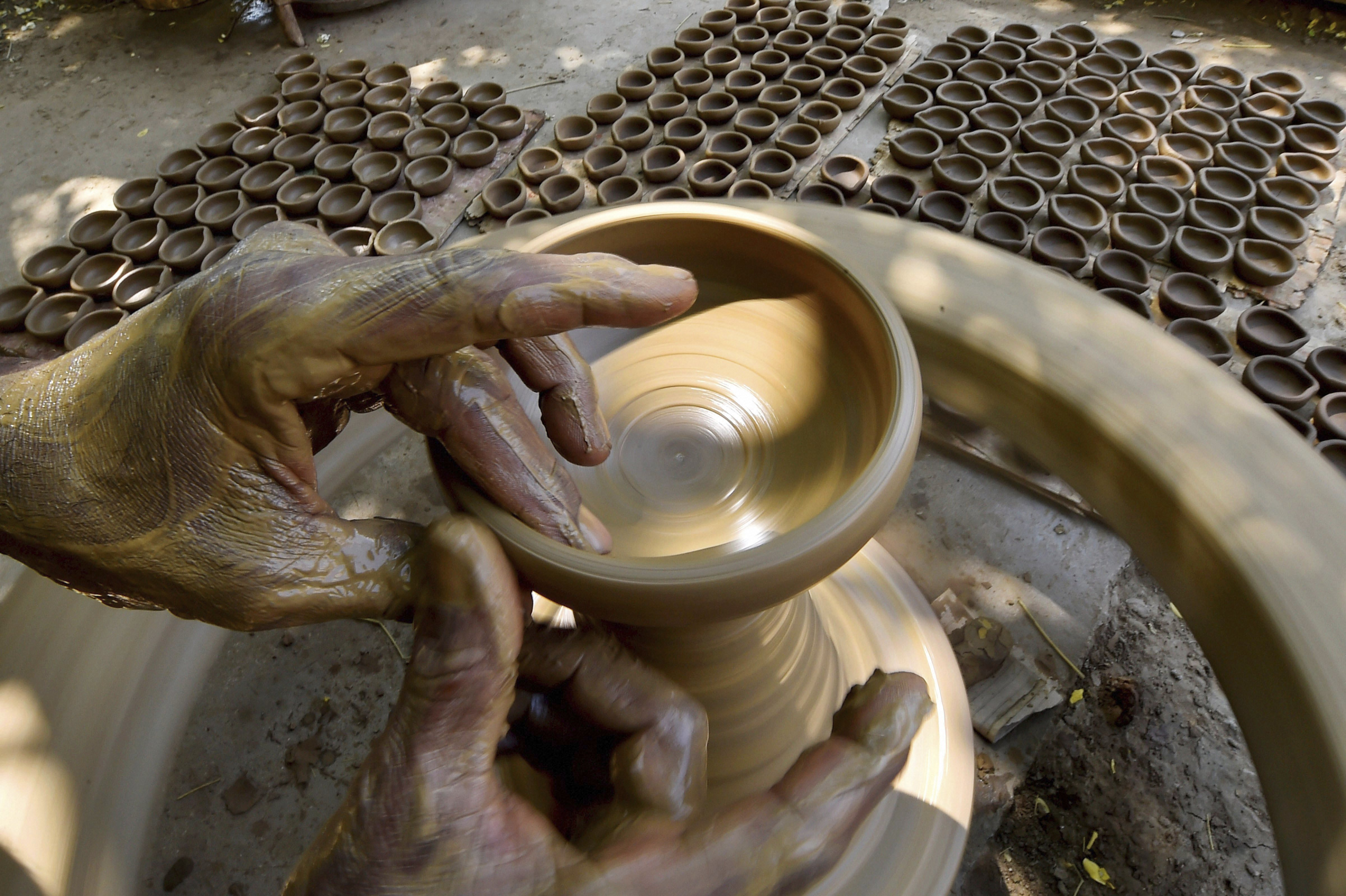 A caly sculpting artisan prepares earthern lamps ahead of Diwali festival celebrations, in Chennai - PTI
