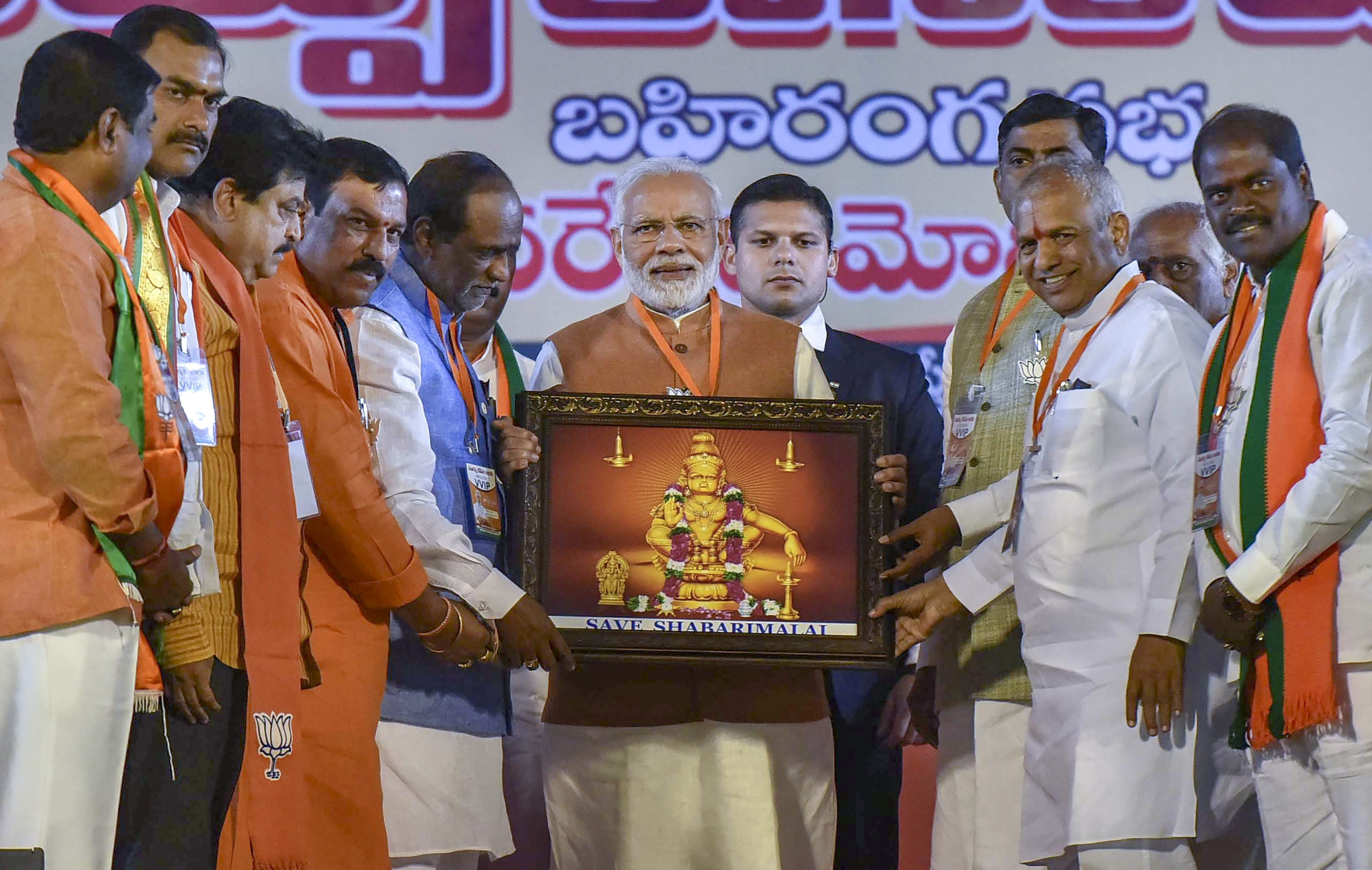 Prime Minister Narendra Modi receives a memento which has an image of Hindu god Ayyappa with 'Save Sabarimala' slogan, during an election campaign rally ahead of the state Assembly elections at LB Stadium, in Hyderabad - PTI