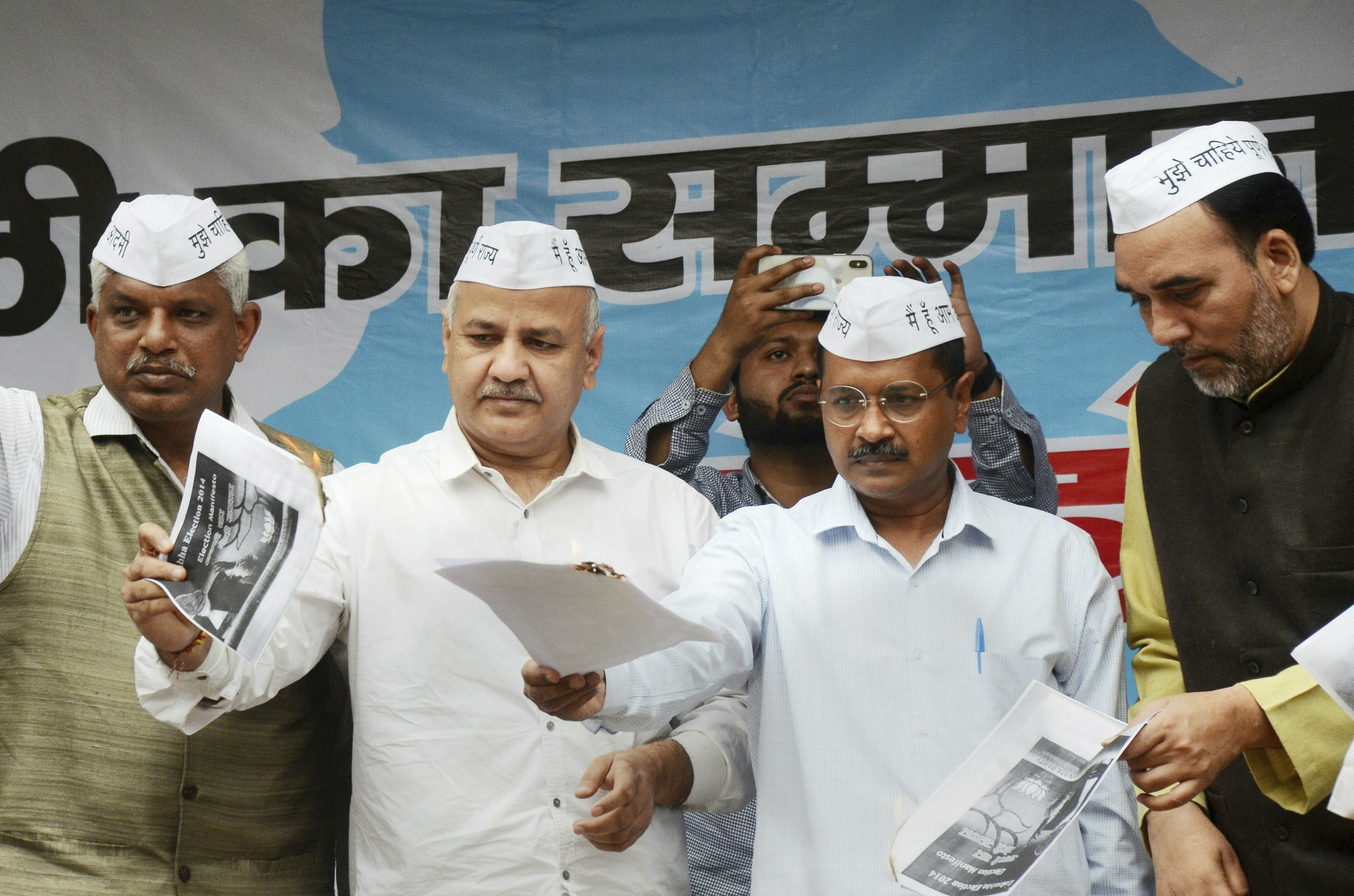 Delhi Chief Minister and AAP convernor Arvind Kejriwal, his deputy Manish Sisodia and other party leaders burn BJP 2014 manifesto in relation to providing full statehood to Delhi - PTI
