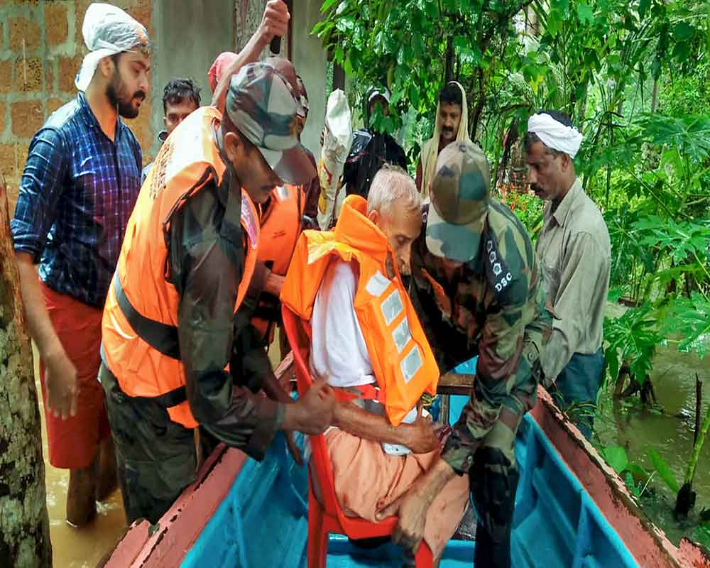 Kozhikode: Personnel from Defence Security Corps rescue residents from a flood-affected area, at Poovattuparamba in Kozhikodedistrict - PTI