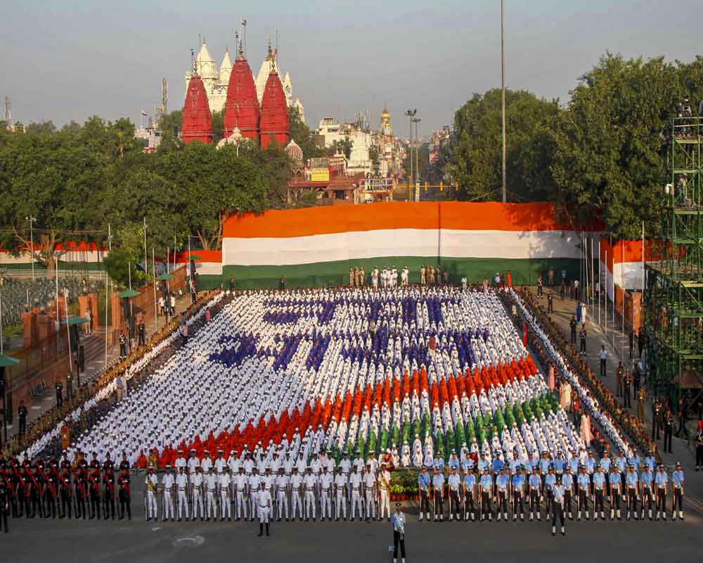 School children make a tricolour during a  rehearsal for the 73rd Independence Day function at the historic Red Fort, in New Delhi - PTI