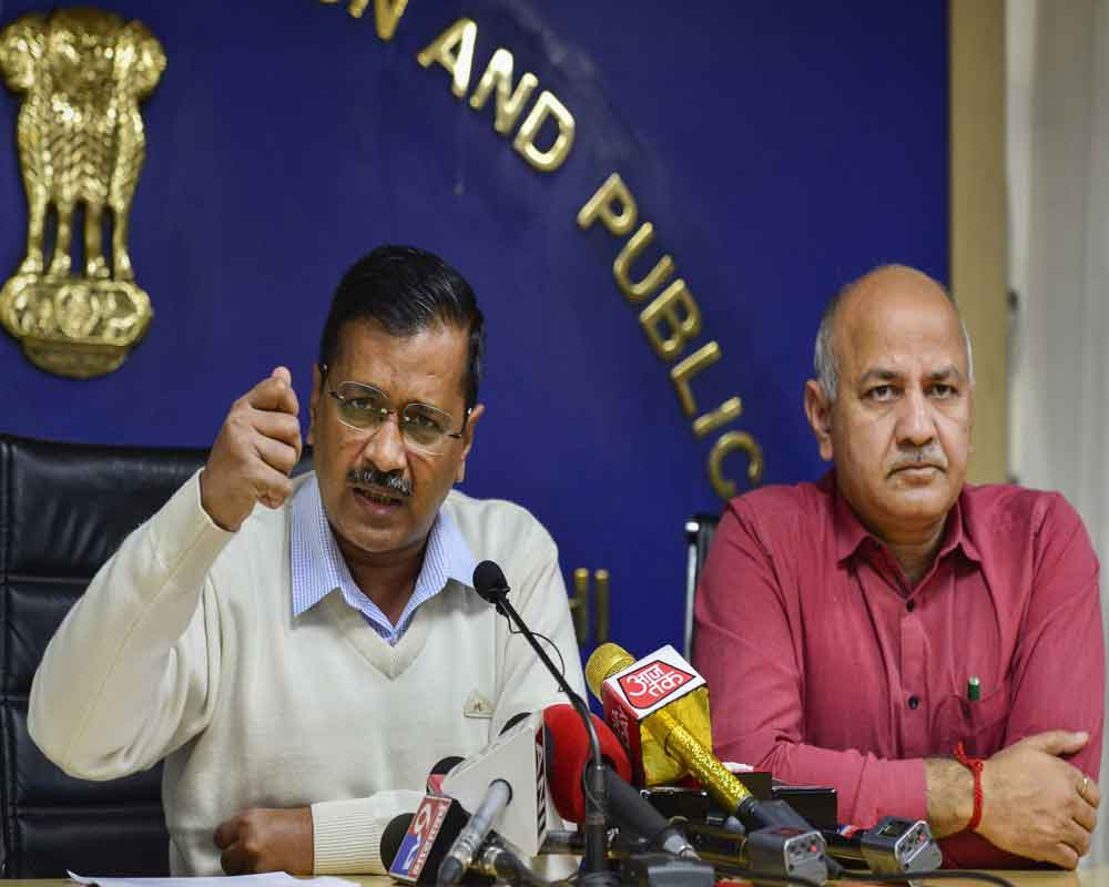 Delhi Chief Minister Arvind Kejriwal addresses a press conference as Deputy Chief Minister Manish Sisodia looks on, in New Delhi - PTI