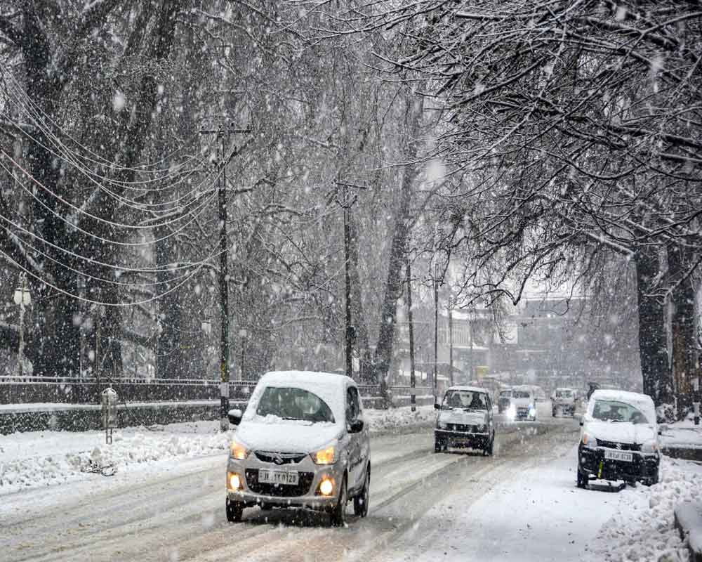 Vehicles moves slowly during heavy snowfall, in Srinagar, Monday, Jan. 13, 2020. Snowfall in Kashmir threw life out of gear for the second day on Monday and forced cancellation of all flights to and fro Srinagar airport - PTI
