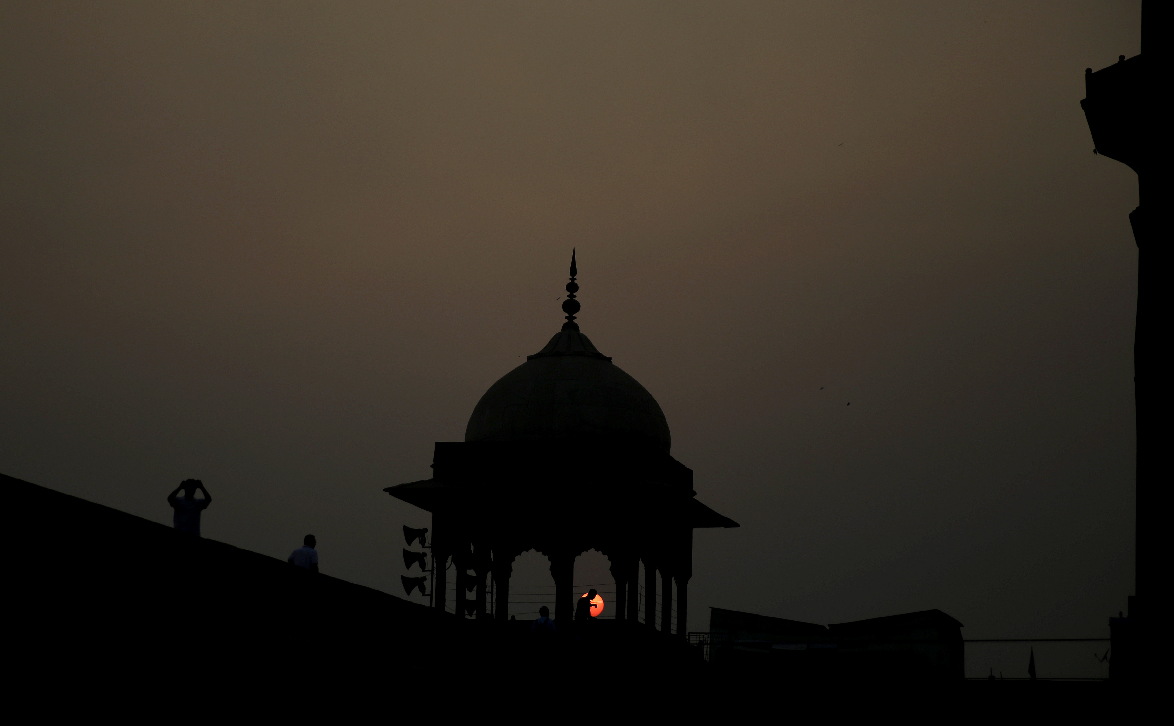 Visitors are silhouetted as sun sets in New Delhi - AP