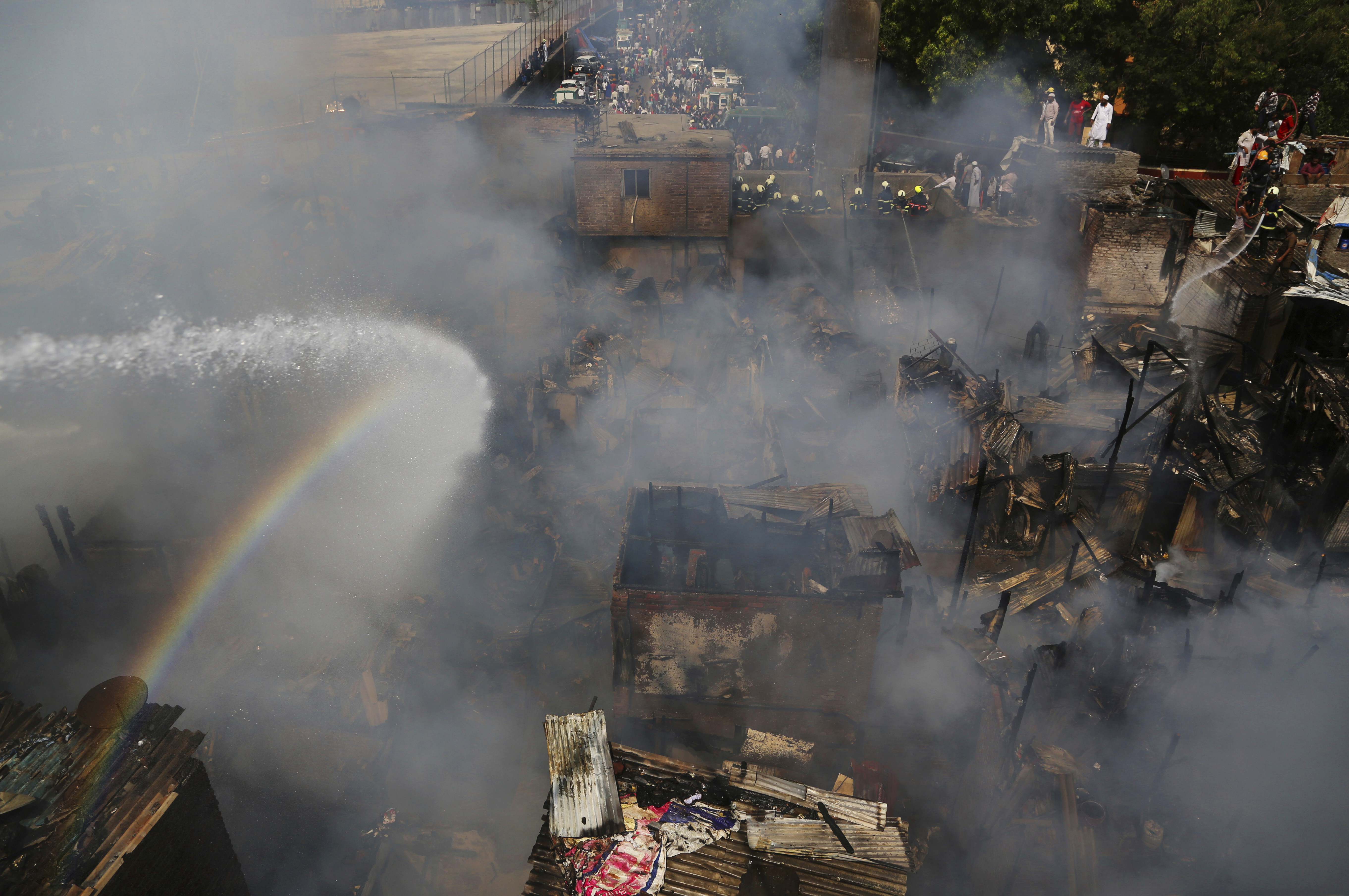 Firefighters try to douse the fire at a slum in Mumbai - AP