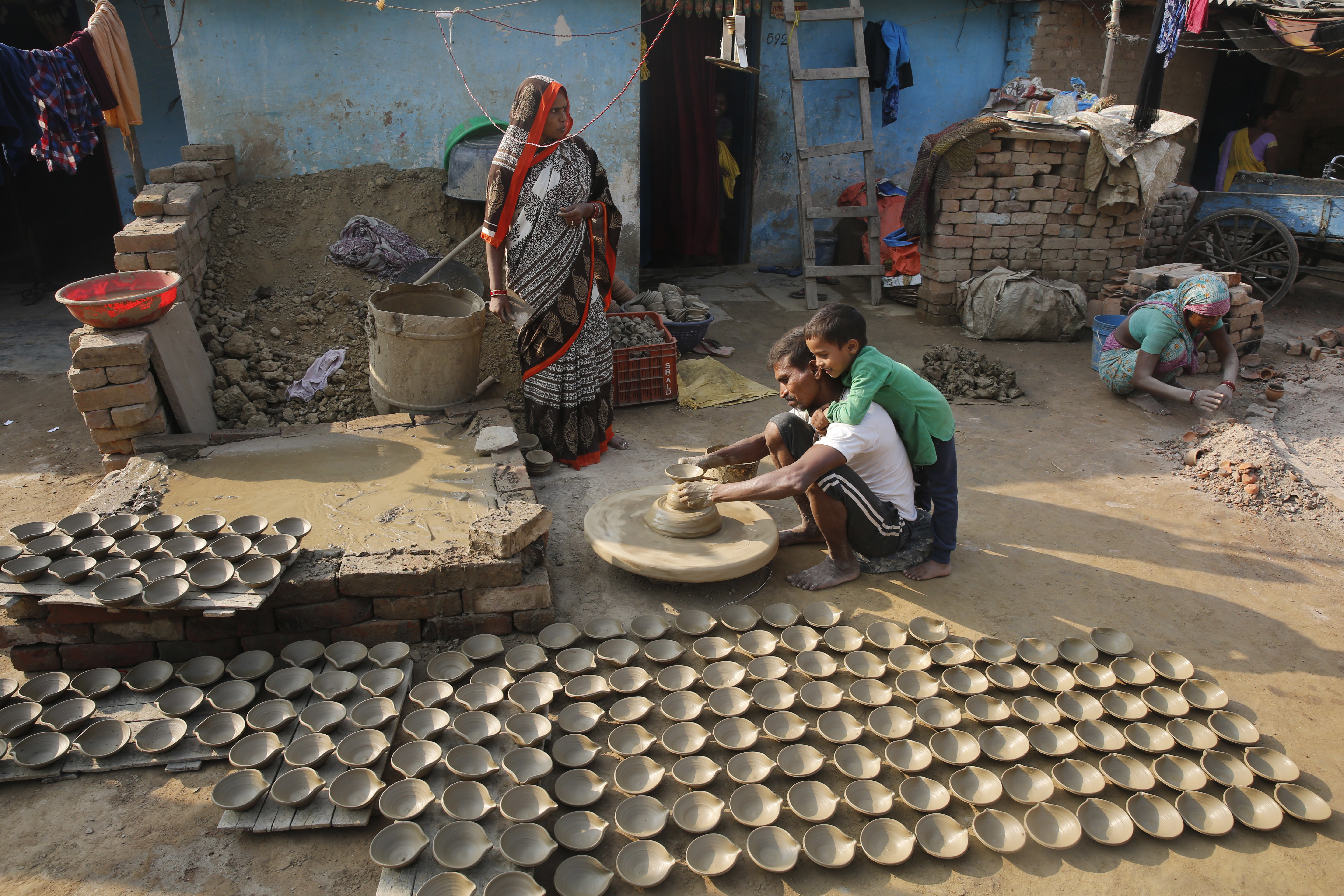 An Indian potter makes earthen lamps ahead of Diwali festival as his son clings on to him in Allahabad-  - AP