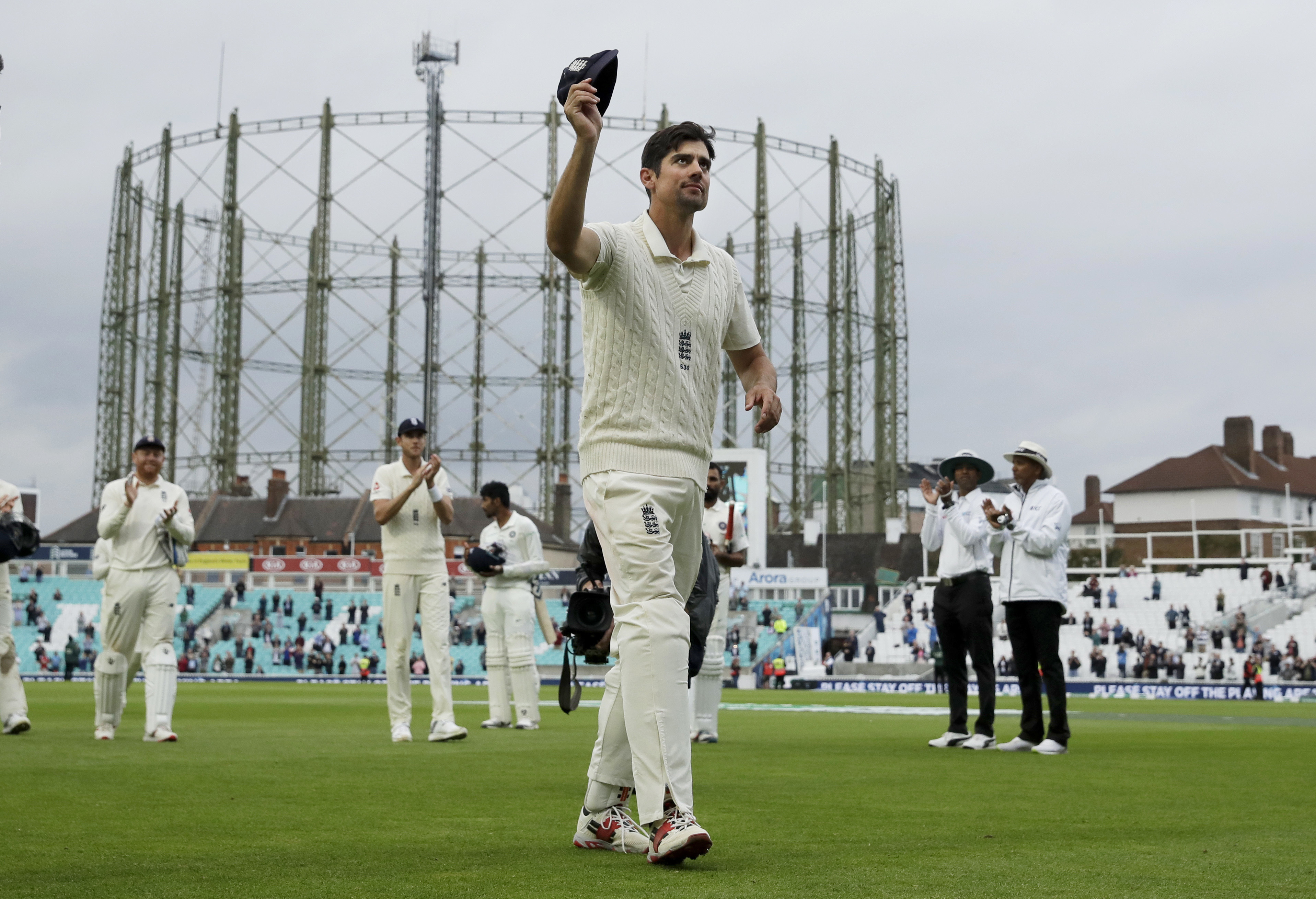 England's Alastair Cook, at the end of his final match before retiring from test cricket, raises his cap as he walks off at the end of the fifth cricket test match of a five match series between England and India at the Oval cricket ground in London - AP