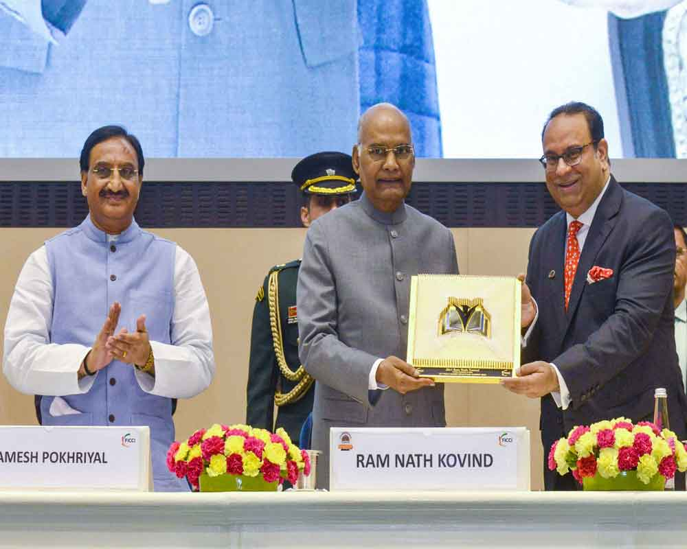 President Ram Nath Kovind receives a memento from FICCI President Sandip Somany as Union HRD Minister Ramesh Pokhriyal Nishank claps during the 15th FICCI Higher Education Summit 2019 - PTI