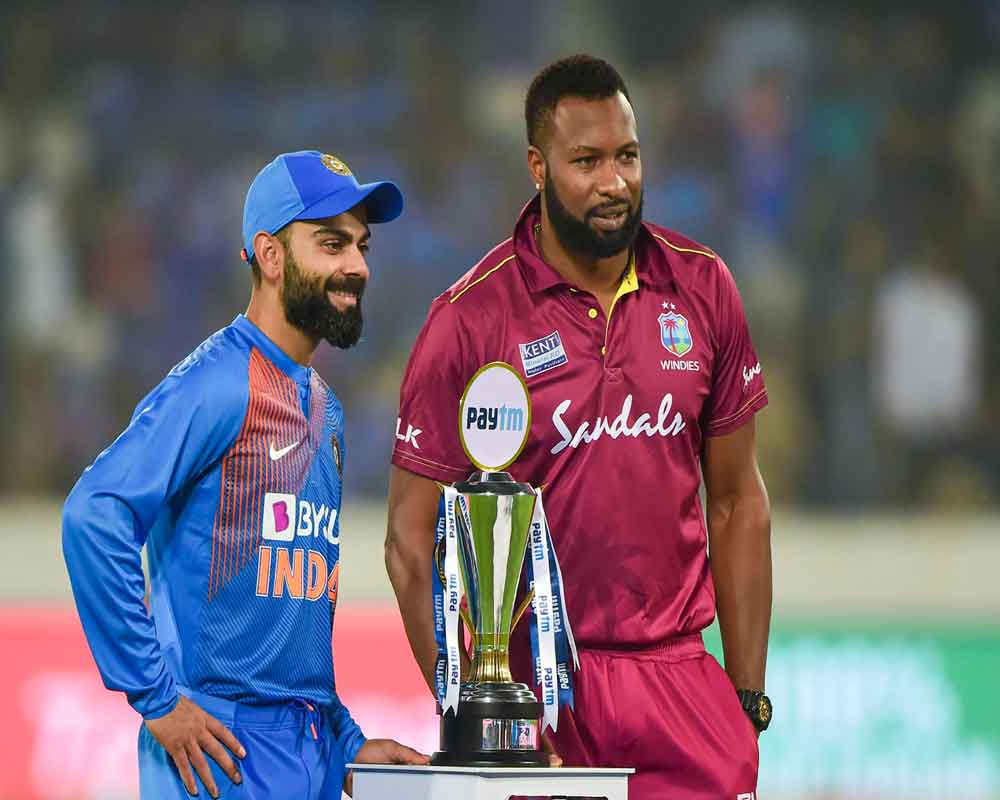 Indian and West Indies skippers Virat Kohli and Kieron Pollard pose with Winner's Trophy prior to the start of the first T20 cricket match, at Rajiv Gandhi International Stadium in Hyderabad - PTI