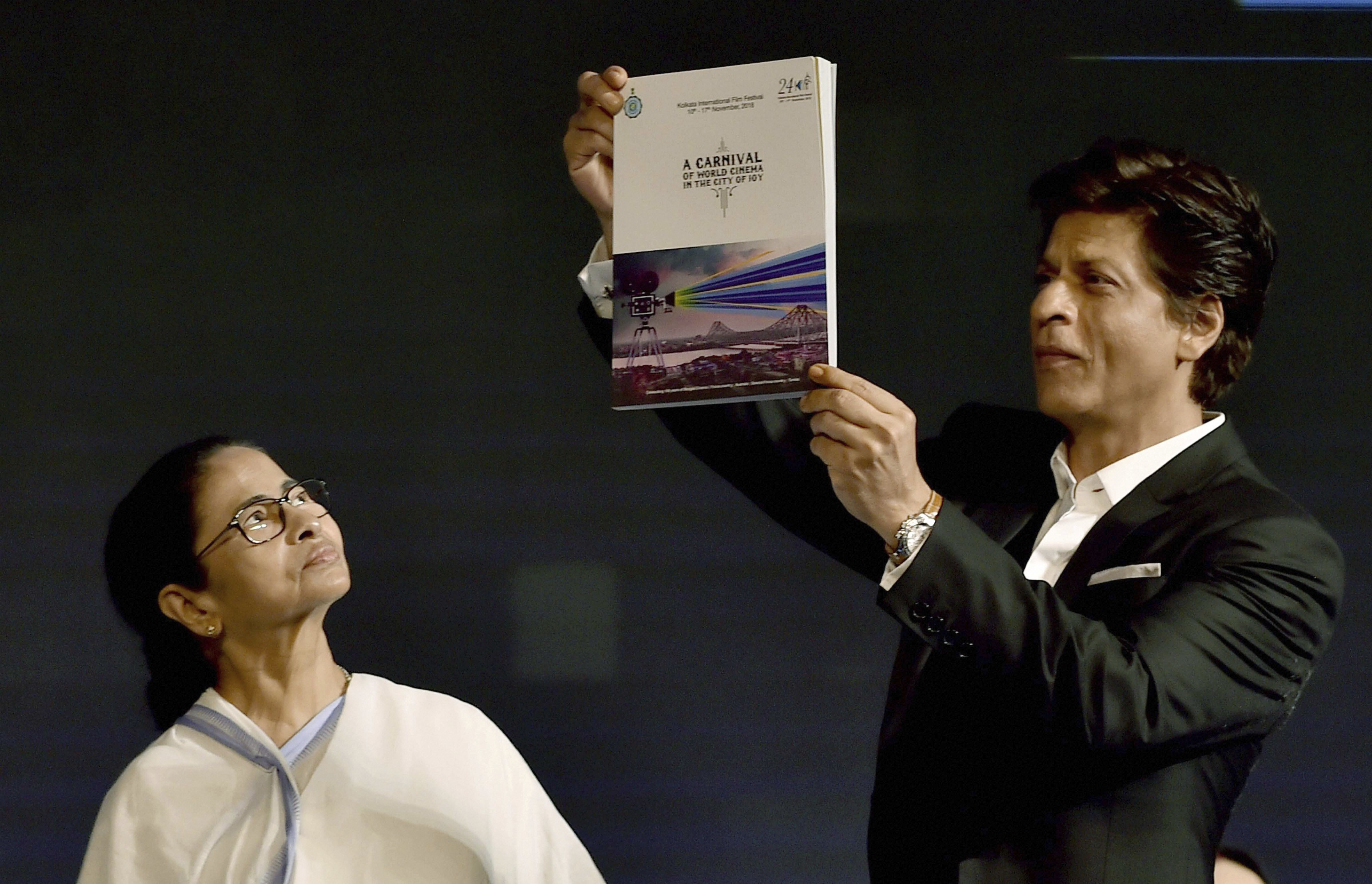 West Bengal Chief Minister Mamata Banerjee looks on as Bollywood actor Shahrukh Khan releases a book during inauguration of '24th Kolkata Intenational Film Festival' in Kolkata - PTI