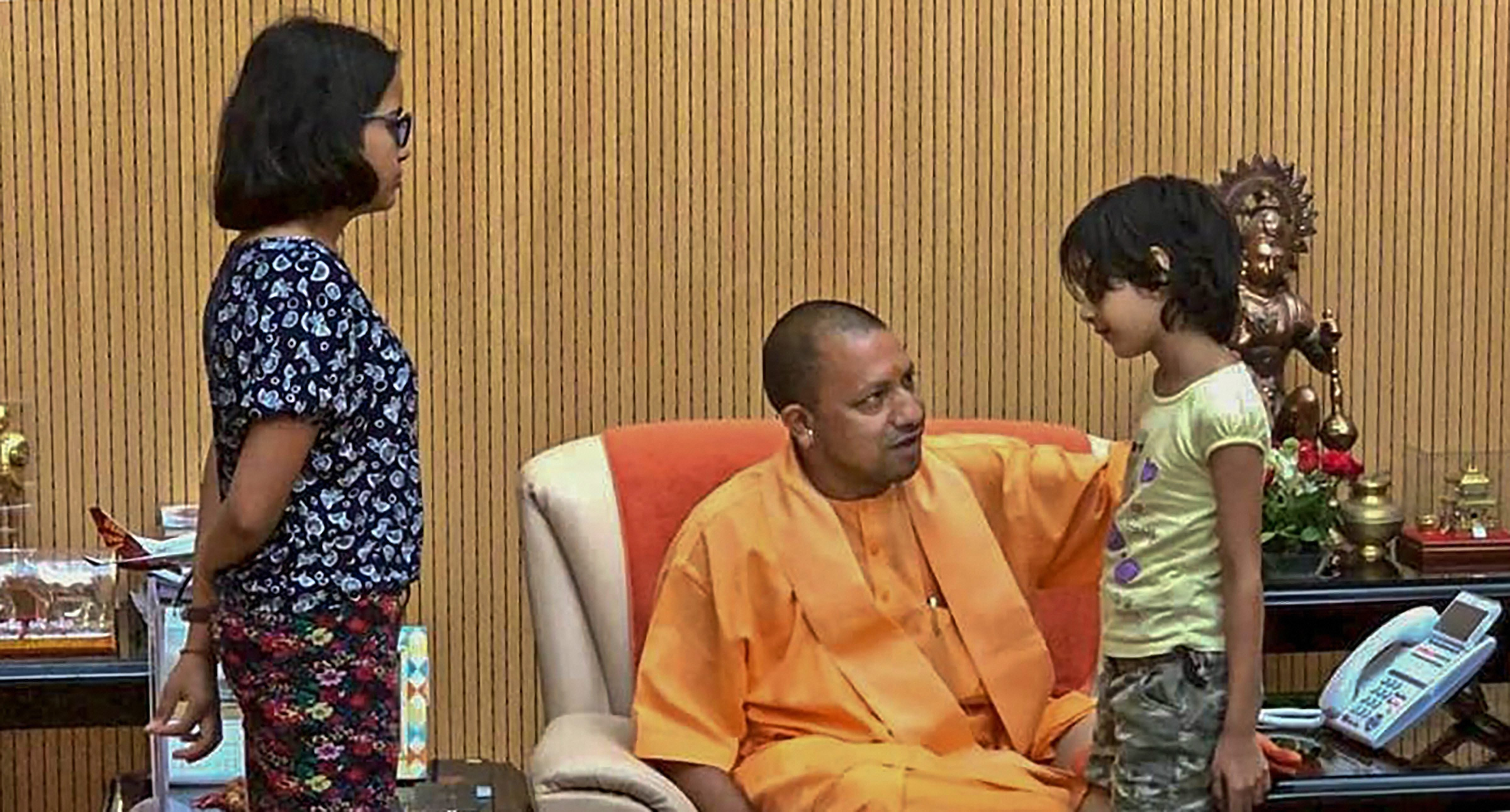 Uttar Pradesh Chief Minister Yogi Adityanath interacts with the children of the private company executive Vivek Tiwari, who was allegedly shot at by a police constable, during a meeting with his family members in Lucknow - PTI