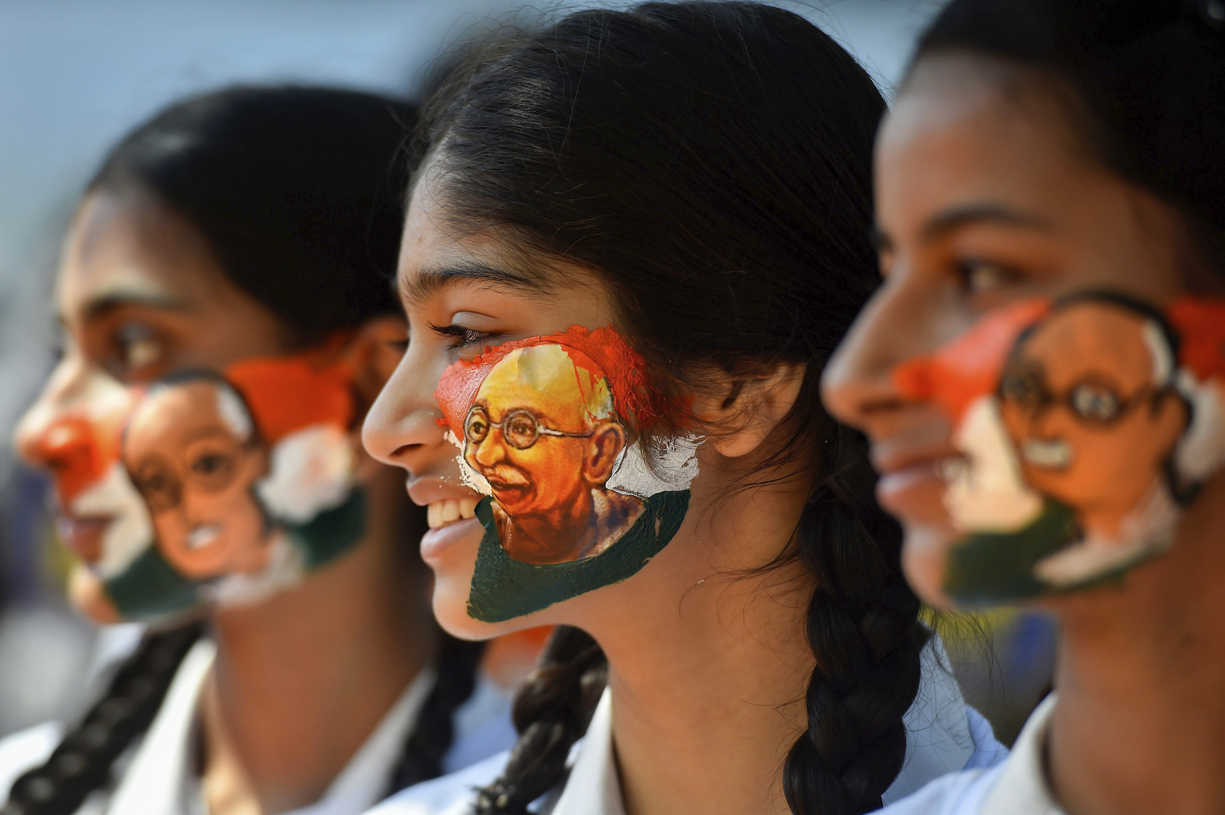 Students paint their face with Mahatma Gandhi image ahead of his birth anniversary, in Chennai - PTI