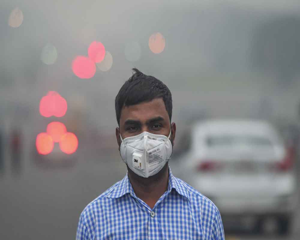 A man wears anti-pollution mask to protect himself from growing level of air pollution, in New Delhi - PTI