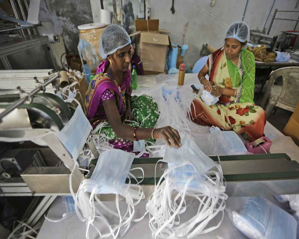Indian laborers work at a surgical mask production unit in Ahmadabad, India. India has banned the export of all varieties of respiratory masks in view of a viral outbreak that began in China which has infected more than 14,550 people globally- PTI