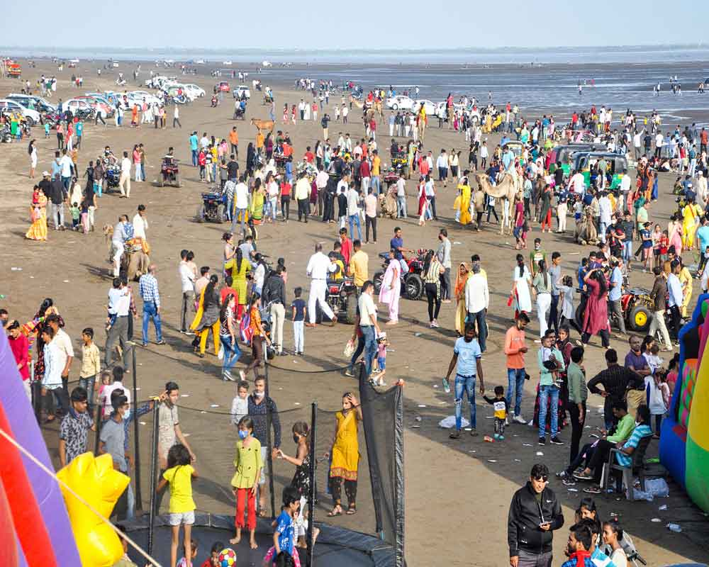 People gather at Dumas Beach after ease in COVID-19 lockdown restrictions, in Surat