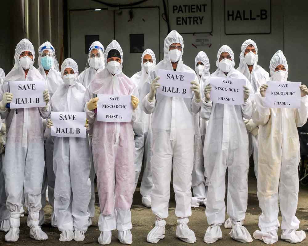 Doctors, nurses and medical staff in PPE kits hold placards during a protest outside Hall C of NESCO jumbo Covid care centre at Goregaon in Mumbai