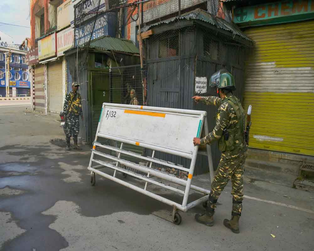 A security personnel pushes a barricade during restriction on fifth consecutive day in Srinagar, Friday, Aug 9, 2019. Restrictions have been imposed in several districts of Jammu and Kashmir as a precautionary measure after the state lost its special status and was bifurcated on Tuesday as Parliament approved a resolution scrapping Article 370 of the Constitution and passed a bill to split the state into two Union Territories - PTI