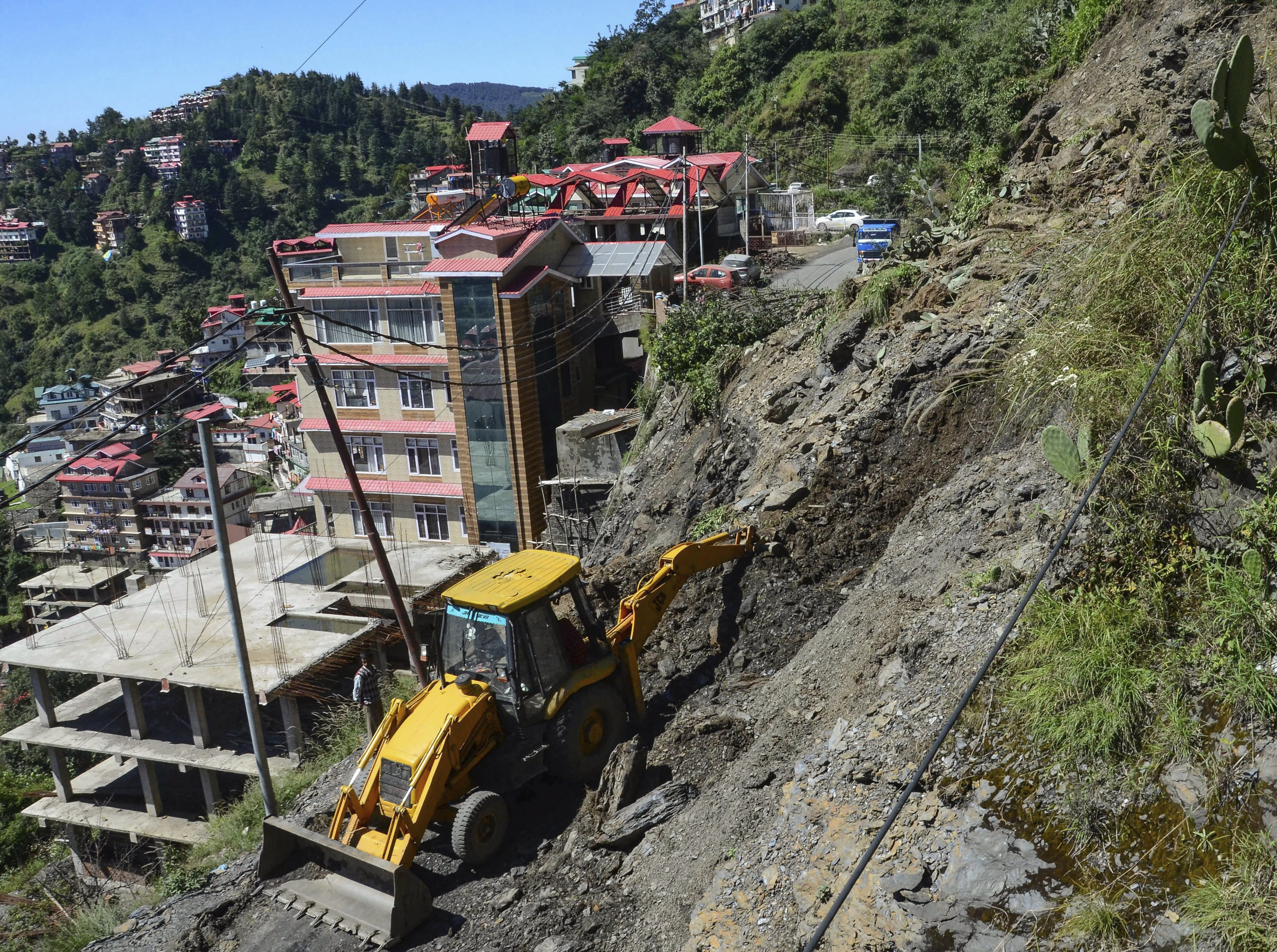 An earthmover clears debris from a road after a landslide triggered by incessant rains, in Shimla - PTI