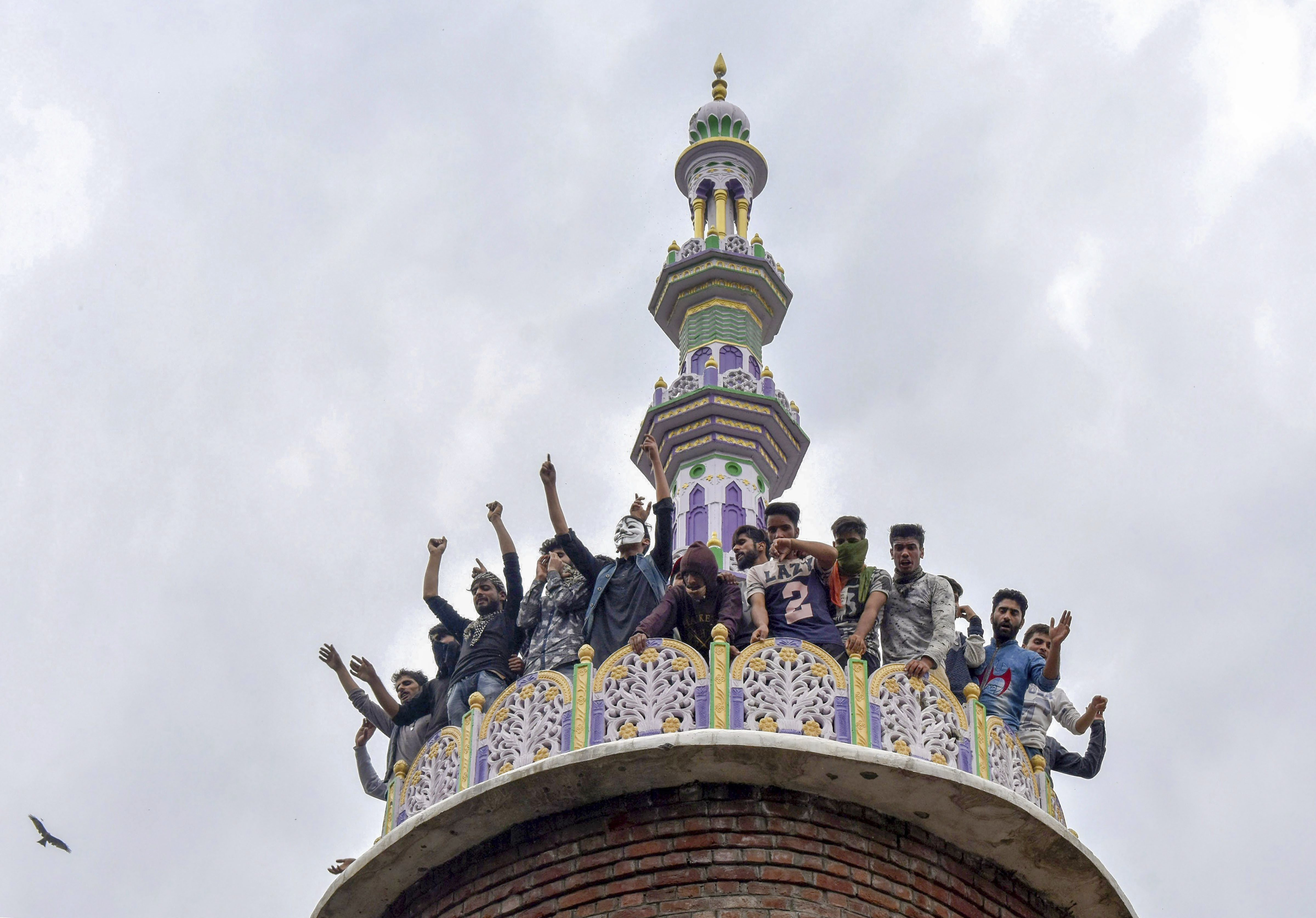 People raise slogans from the tomb of a mosque, where militants were hiding during an encounter with security forces, at Panzan Chadoora area of Budgam district near Srinagar - PTI