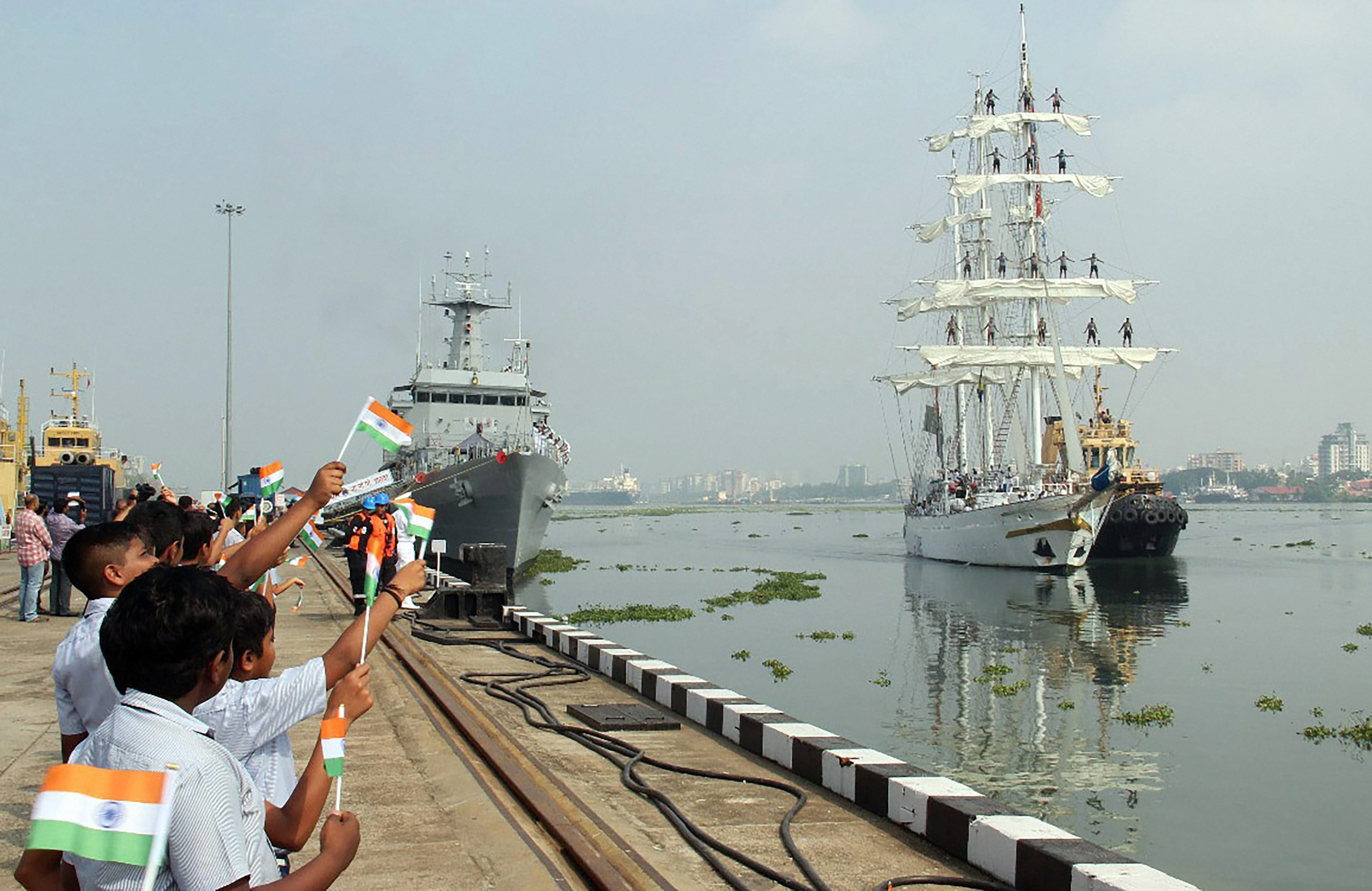 School children wave the Indian tricolour to welcome INS Tarangini which returned to Southern Naval Command, in Kochi - PTI