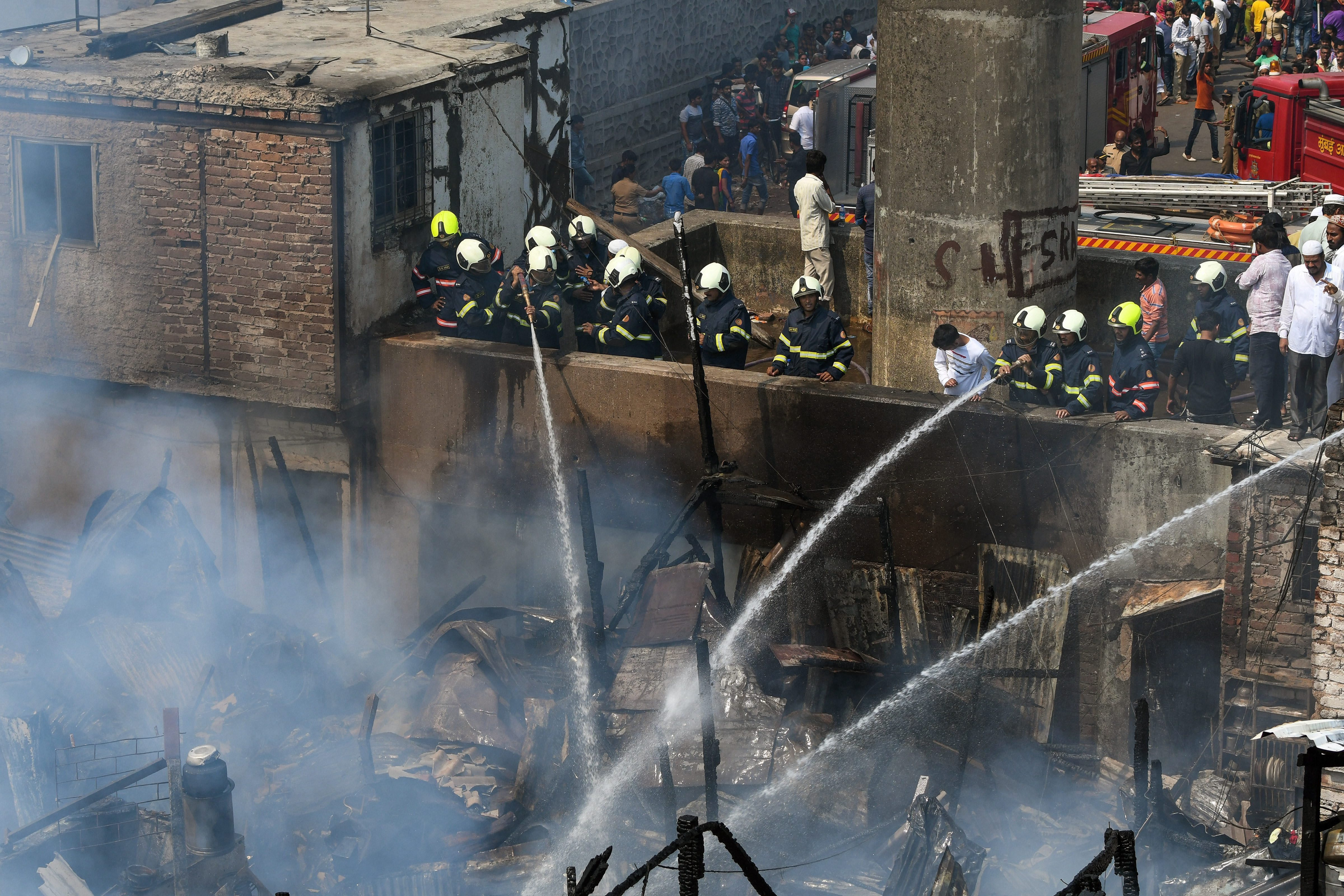 Fire and emergency personnel try to douse a fire at Nargis Dutt Nagar slums in suburban Bandra, Mumbai - PTI