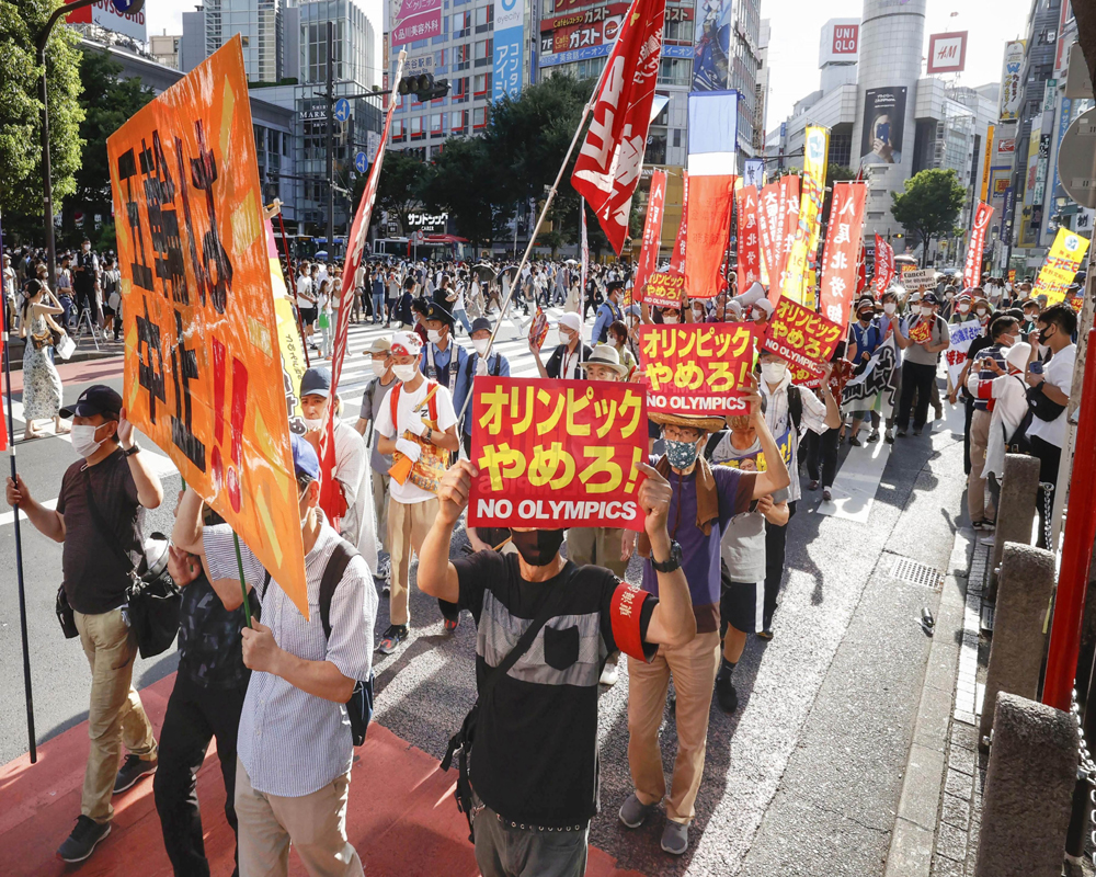 Anti-Olympics protesters march with banners through Shibuya district in Tokyo on the opening day of the Tokyo 2020 Olympics.