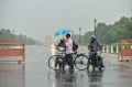 Today's Photo : A cyclist holding an umbrella crosses a road during rainfall
