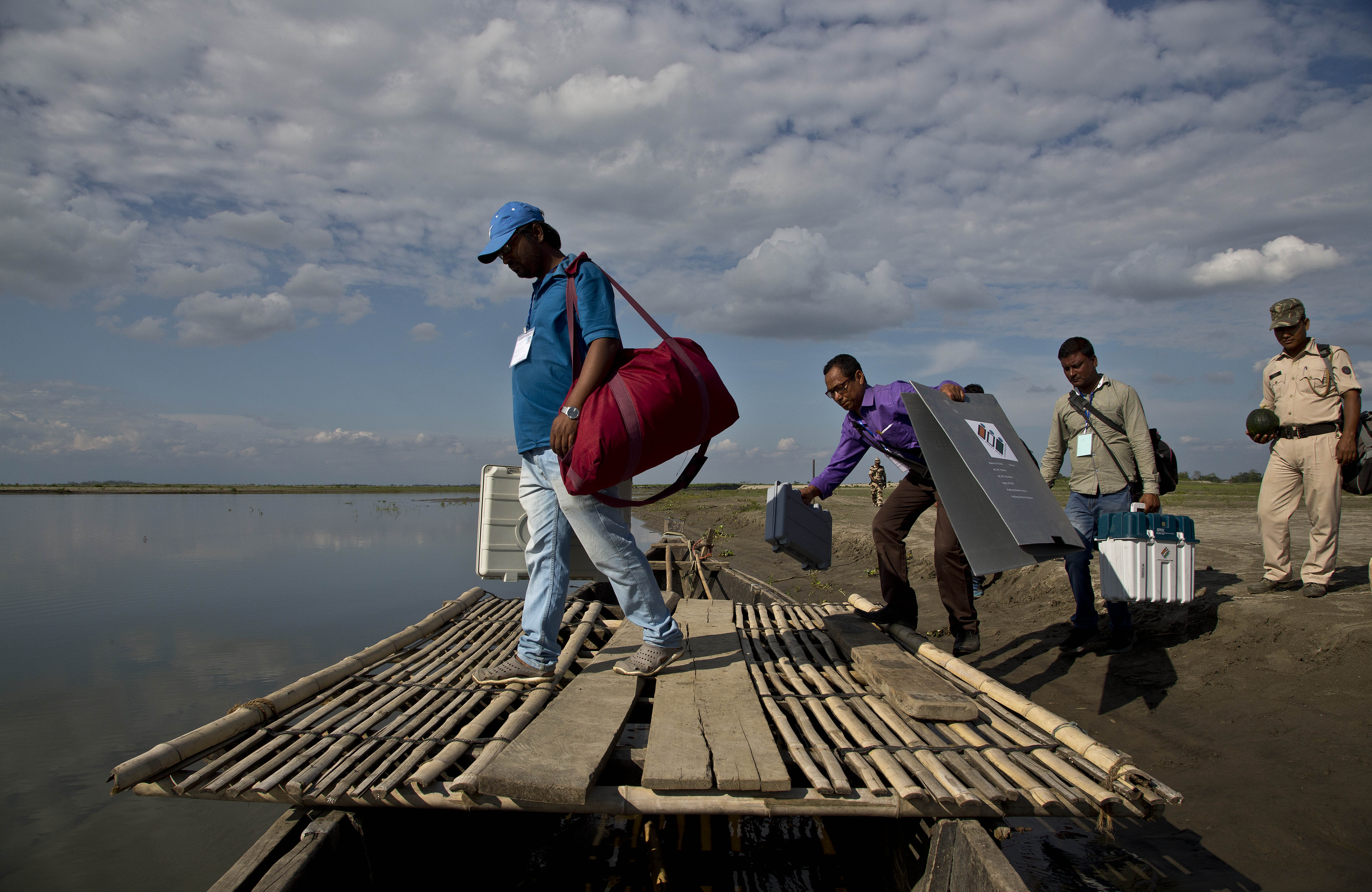 Indian election officials and paramilitary soldiers with election materials board on a country boat to cross the river Brahmaputra on the eve of first phase of general election in Majuli, Assam - AP